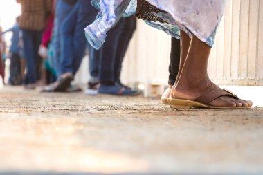 Crowd of people standing wearing sandals in Colombo, Sri Lanka.