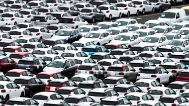 Many cars at a dealership yard at a port in Reunion, waiting to get through customs.