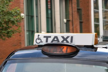 A taxi sign with a disable - wheelchair symbol in Belfast, Northern Ireland, UK.
