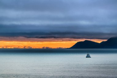 Scenery of a small ship on the Bering sea and the St Lawrence island in the background at dusk on a stormy day, Alaska.