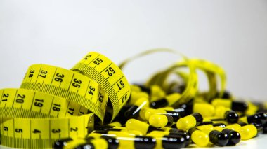 Pills with measuring tape on white background, represent the diet pill industry