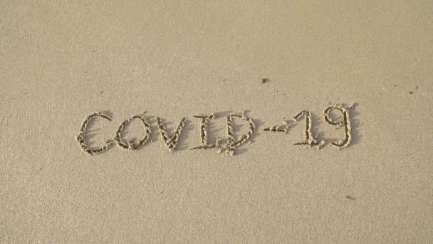 4K, Covid-19 geschrieben auf dem Sand des Uferstrandes mit einströmender Wellenwäsche, die während des Coronavirus-Sommers gelöscht oder storniert wird. Angst vor dem Urlaub wegen der Pandemie des covid 19-Dan