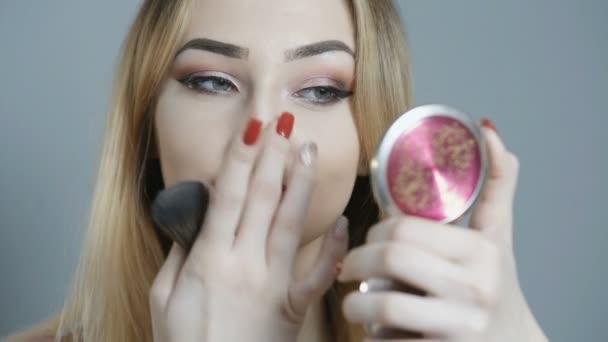 szép lány csinál smink, fiatal nő elkenődött Matt rúzs a applikátor a színes háttér, a koncepció a kozmetikai és szépségápolási