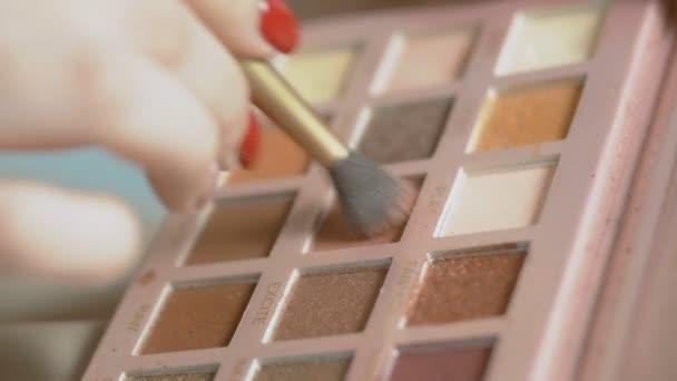 ruka mladé dívky zachytí stín oka štětcem z palety a příliš se rozběhne, žena dělá makeup kosmetiky, koncept krásy a životní styl mládí