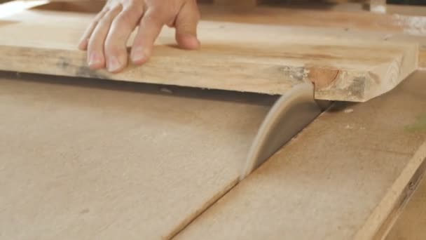 young man cuts a wooden board with a circular saw blade, a workshop with a professional tool for woodworking, a concept of construction working process of manufacturing parts for construction