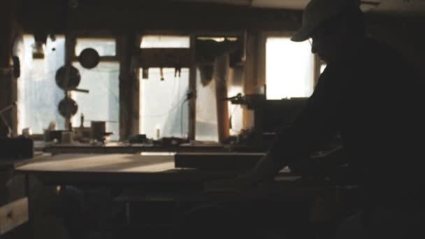 Obrázek silueta mladého muže řezání dřevěné desky s kruhovým pilovým kotoučem v ochranných brýlích, dílna s profesionálním nářadím, koncept stavby