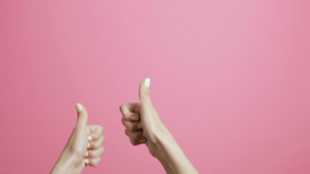 young womans hands show thumbs up, girl advertises showing gesture class on pink studio background
