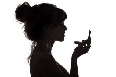 silhouette of woman admiring herself in a mirror, profile of a woman face, concept of fashion and beauty