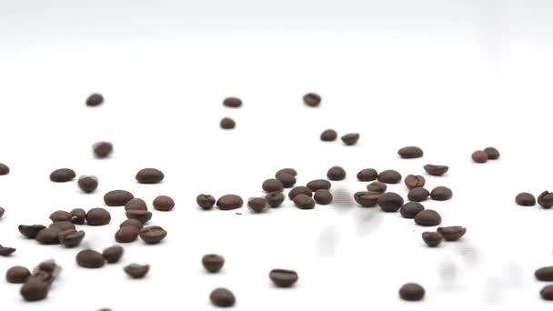 Kaffeebohnen fallen Filmmaterial auf weißem Hintergrund