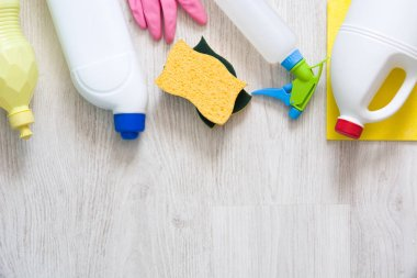 Cleaning items on white floor in the house. Flat lay top-down composition. Copyspace