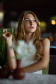 Girl with blue eyes sitting on urban cafe. woman with brown wavy hairstyle. Lifestyle concept.