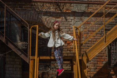 Tracking shot of little girl in linen dress lying on railing of staircase and sliding down