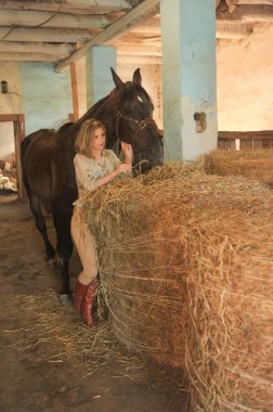 Young girl and horse. Girl and horse in horse stall. Man and animal concept. Portrait of a girl of 15 years old. Horse in the stable.