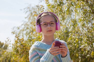 Schoolgirl with backpack in headphones at the park. A schoolgirl in pink headphones listens to music after school. Autumn school childhood. Portrait of a girl of 9 years old
