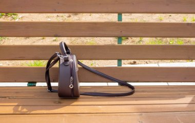 A womans brown purse is lying on a light brown bench . Space for your text.