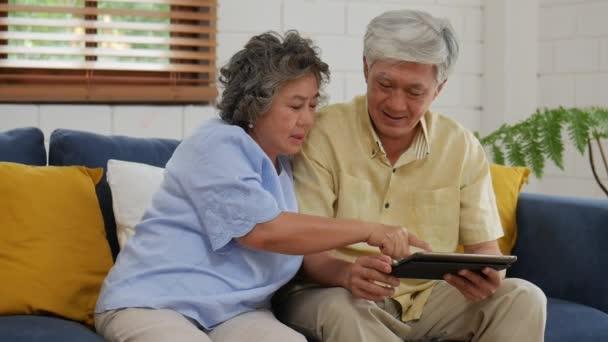 asiatische Senioren-Paar mit Tablet-Suche Online-Shopping. Kommunikation in den sozialen Medien zu Hause auf dem Sofa.