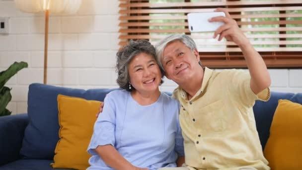 Asijští vysocí mají videokonverzaci pomocí telefonu Smartphone. Sdílení společenských mediálních komunikací, které sedí na pohovce doma. Zpomaleně