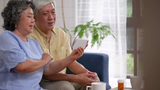 Asijský starší pár s lékařskou poradmou v mobilním rozhovoru. Sdílení společenských mediálních komunikací, které sedí na pohovce doma. Zpomaleně.