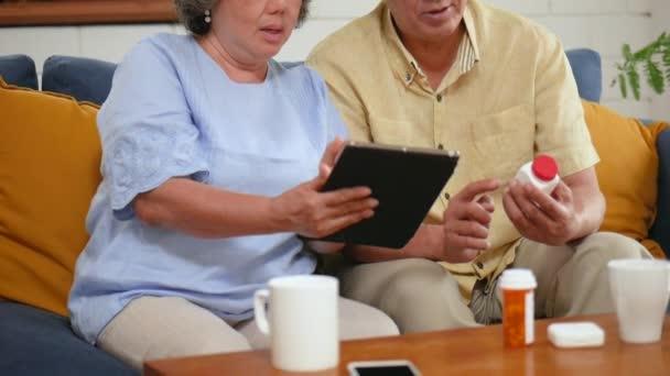 Asijský starší pár hledá lékařskou konzultaci na tabletu. Sdílení společenské mediální komunikace a posezení na pohovce doma. Zpomaleně
