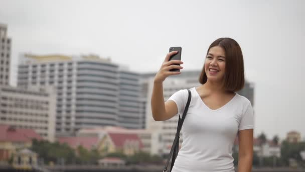Beautiful young Asian woman having video chat using smartphones connecting with friends on social media summer vacation.