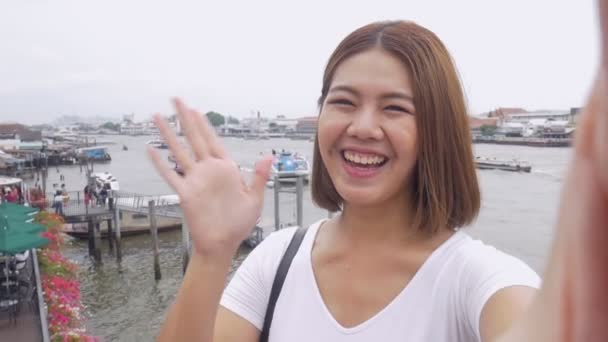 Smile beautiful Asian woman taking selfies on a smartphone. Young Asian girl tourist travel to Thailand.