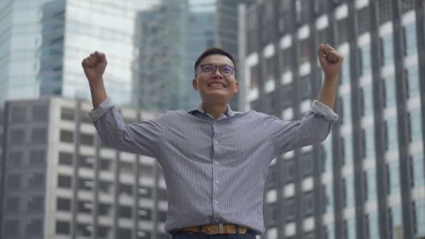 Porträt gutaussehender asiatischer Geschäftsmann, der nach einem Arbeitsleben Erfolg und Erfolg hat und sich in einer urbanen Stadt umsieht. Zeitlupentempo-Aufnahmen.