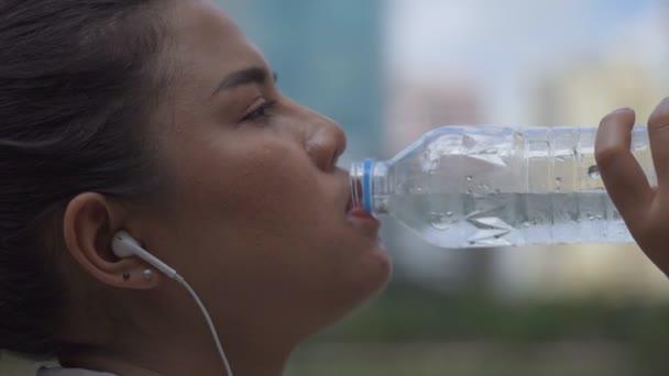 Közelről portré fiatal ázsiai nő futó ital a víz futtatása után. Sportswomen fut az egészséges életmód.