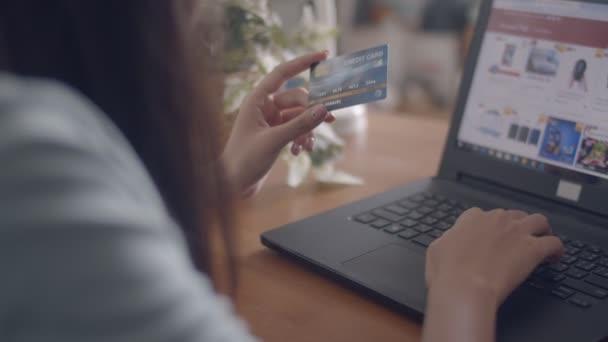 Közelről fiatal ázsiai nő laptop vásárlás segítségével online hitelkártyával otthon.