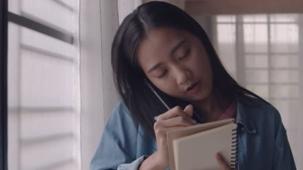 Young Asian businesswoman standing beside window talking on the phone and taking notes ideas planning strategy at home office.