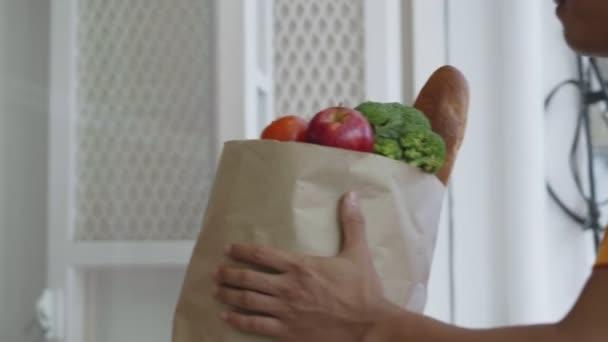 Poslíček, který dává jídlo ženě zákazníka doma.