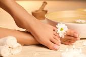 Das Bild der idealen Maniküre und Pediküre. Frauenhände und -beine im Wellnessbereich.