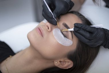Beautiful woman in a beauty saloon doing eyelashes. Eyelash Extension