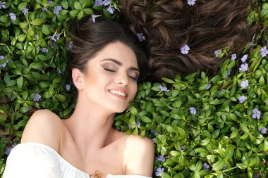 Close up of woman lying down on the grass. Beautiful make up and shiny hair in nature.