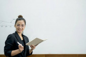Eine asiatische Lehrerin in einem Klassenzimmer in der Nähe des Whiteboards schreibt und unterrichtet eine Lektion mit einem speziellen Vortrag in einer Klassenkolumne. Mathelehrer erklärt Studenten Rechensummen.