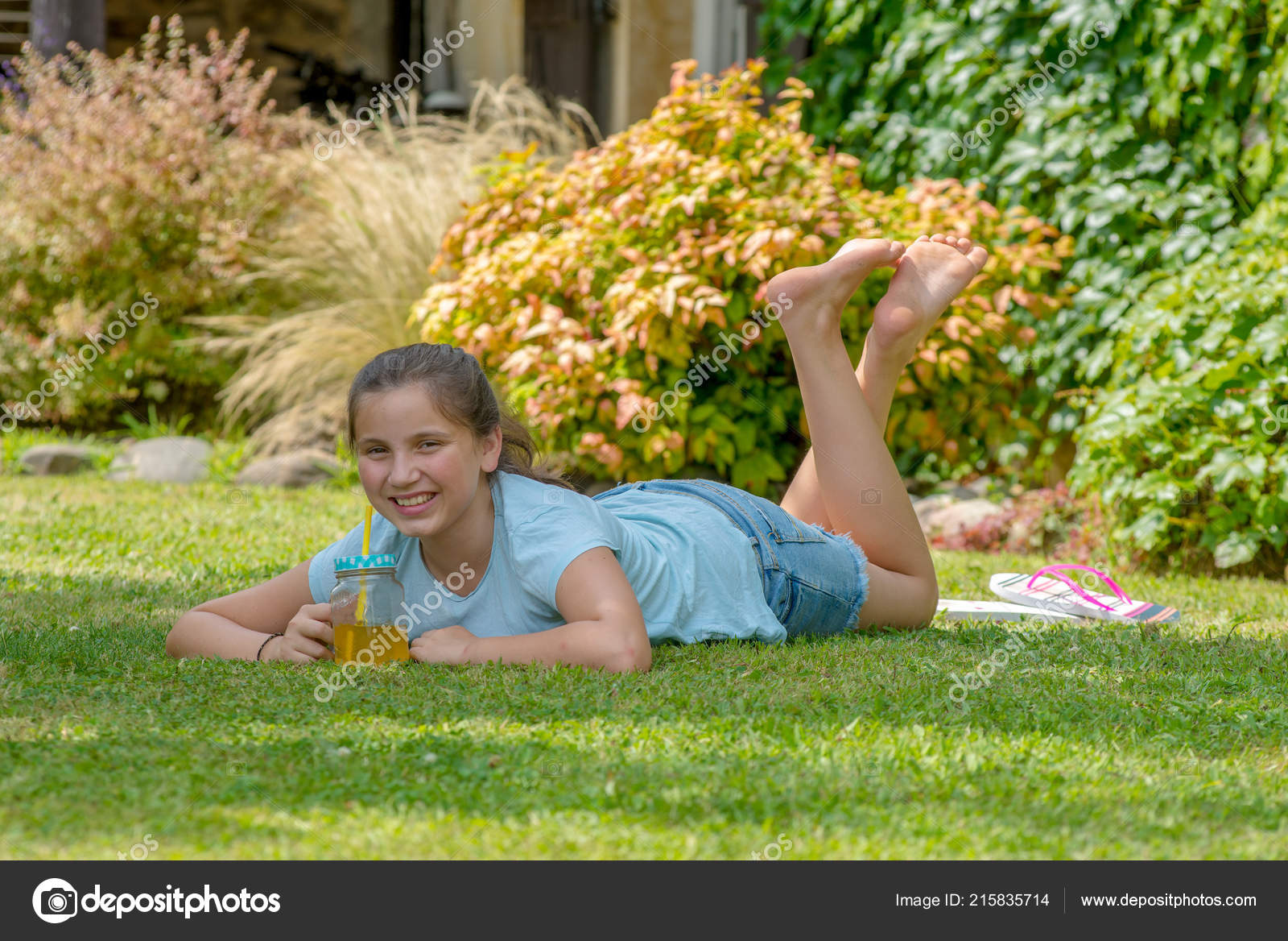 Outdoor portrait of a cute young black girl lying down on
