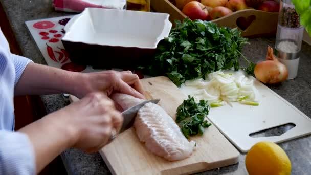 Příprava čerstvých ryb, syrové treska filety s přidáním bylinek a citronem