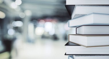 Stacked books on blurry bokeh background with copy space. Education and library concept. 3D Rendering