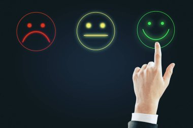 Hand with smiley rating on dark background. Excellent service concept