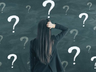 Back view of young businesswoman on chalkboard wall background with question marks. Confusion and solution concept