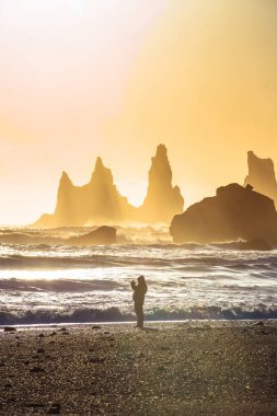 Reynisdrangar, basalt sea stacks at foot of mountain Reynisfjall, legend of two trolls dragged a three-masted ship to land and daylight broke they became needles of rock