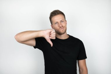 handsome young man wearing black t-shirt showing dislike with negative expression isolated white background