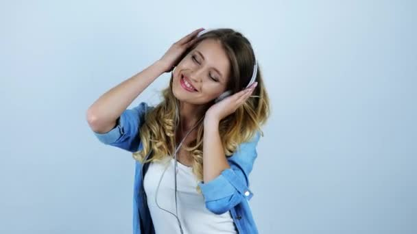 young beautiful sexy blonde woman enjoying favourite songs in headphones on isolated white background