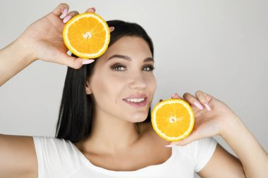 young brunette woman holding two fresh halves of orange near her beautiful face on isolated white background