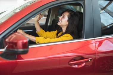 beautiful brunette woman looking for new car in dealership center checking the interior