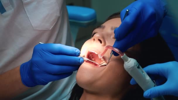 dentist in gloves sealing patient womans teeth using dental mirror , dam and ejector during appointment in dental clinic