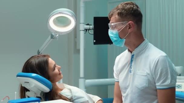 junge hübsche Zahnärztin in medizinisch blauen Handschuhen, Maske und Brille spricht mit der schönen Patientin vor Beginn der Untersuchung während des Termins in der Zahnklinik