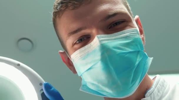 mladý hezký usmívající se lékař zubař v masce drží lékařské lampy a používá zubní zrcadlo při vyšetření pacientů