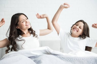 young beautiful mother and her cute teen daughter just woke up together sitting in bed stretching