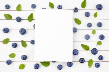 Framework made of blueberry on white wooden background. Flat lay. Food concept.