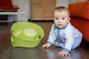 Portrait of an innocent baby boy sitting on floor in room near flipped over potty.